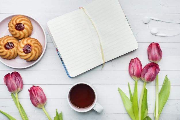Zasięrzutny widok bukiet tulipanów i notatnika i filiżanka kawy.