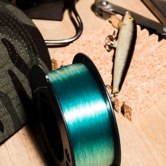 Zasięrzutny widok kołowrotek wędkarski i przynęty wędkarskie na powierzchni drewnianej