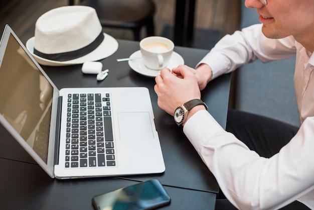 Zasięrzutny widok młody człowiek patrzeje laptop z kawą; kapelusz i telefon komórkowy na stole