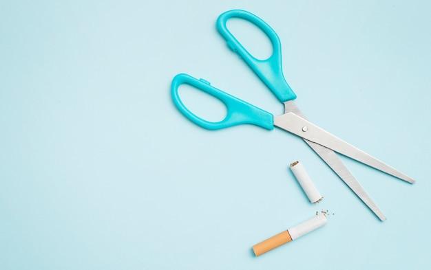 Zasięrzutny widok nożycowy i łamany papieros na barwionym tle