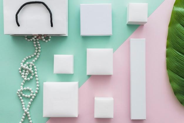 Zasięrzutny widok perła kolia z wiele białymi pudełkami na papierowym tle