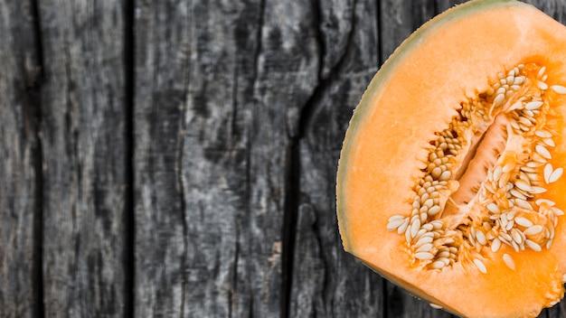 Zasięrzutny widok połówki piżma melon na starym drewnianym tle