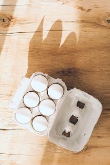 Zasięrzutny widok spadać na białym jajko kartonie na drewnianym tle światło słoneczne