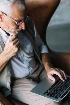 Zasięrzutny widok starszego mężczyzna obsiadanie na krześle używa laptop