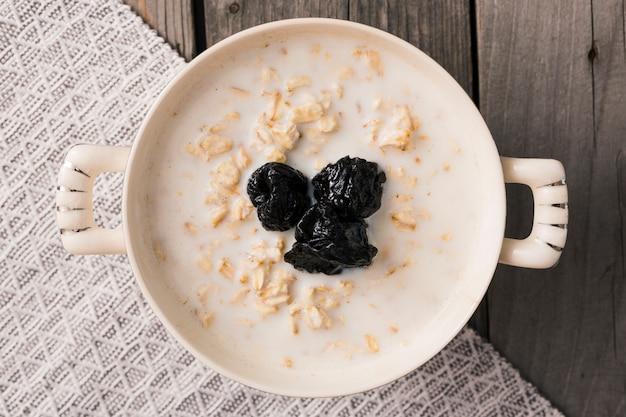 Zasięrzutny widok suche śliwkowe polewy na oatmeal w pucharze