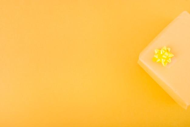 Zasięrzutny widok teraźniejszy prezenta pudełko nad żółtym tłem