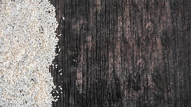 Zasięrzutny widok uncooked biali ryż na czarnym drewnianym textured tle