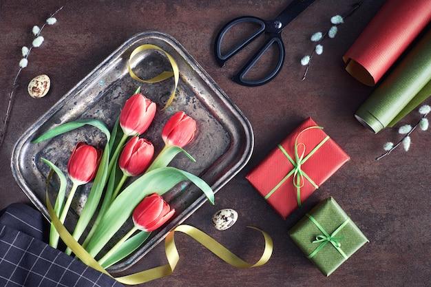 Zasięrzutny widok wiosennych dekoracji: zawinięte prezenty, kwiaty wierzby i tulipanów na ciemnym tle
