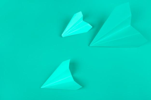 Zasięrzutny widok zielonych papierowych samolotów na miętowym tle