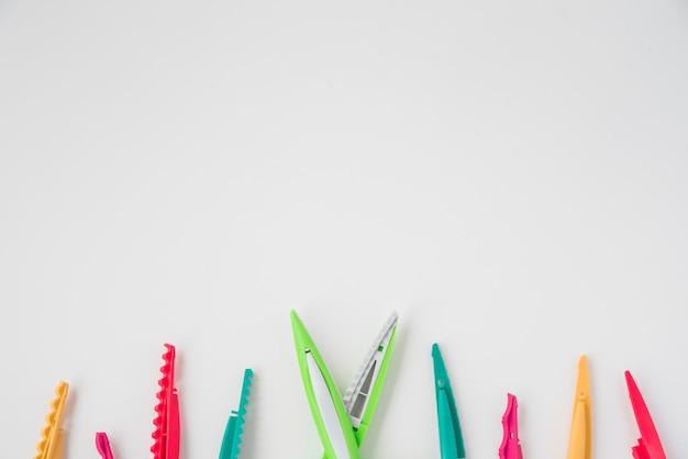 Zasięrzutny widok zygzakowaty nożycowy z kolorowymi ostrzami przy dnem biały tło