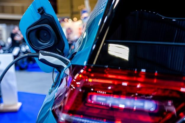 Zasilacz do ładowania samochodu elektrycznego, stacja ładowania samochodu elektrycznego, zbliżenie zasilacza podłączonego do ładowanego samochodu elektrycznego