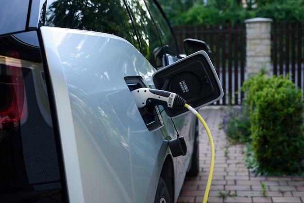 Zasilanie stacji ładowania samochodów elektrycznych połączone z ładowanym nowoczesnym samochodem elektrycznym