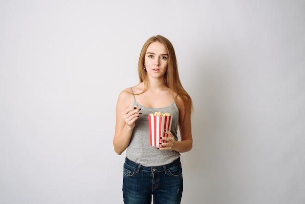 Zaskakująca kobieta je popcorn. dziewczyna trzyma duże pasiaste pudełko z kinową porcją kukurydzy pop. łał