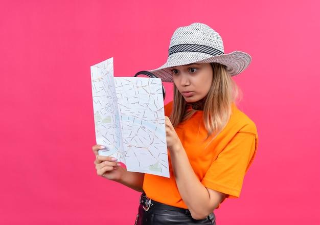 Zaskakująca, ładna młoda kobieta w pomarańczowej koszulce w kapeluszu przeciwsłonecznym, patrząc na mapę przez lupę