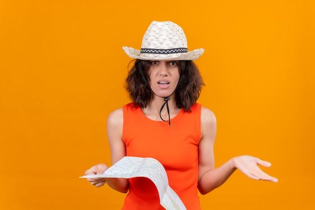 Zaskakująca, ładna młoda kobieta z krótkimi włosami w pomarańczowej koszuli w kapeluszu przeciwsłonecznym i trzymająca mapę