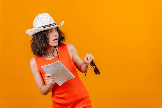 Zaskakująca młoda kobieta z krótkimi włosami w pomarańczowej koszuli w kapeluszu przeciwsłonecznym trzymająca mapę, patrząc zaskakująco w bok