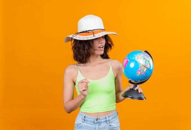 Zaskakująca młoda kobieta z krótkimi włosami w zielonej bluzce, w kapeluszu przeciwsłonecznym, patrząc na kulę ziemską