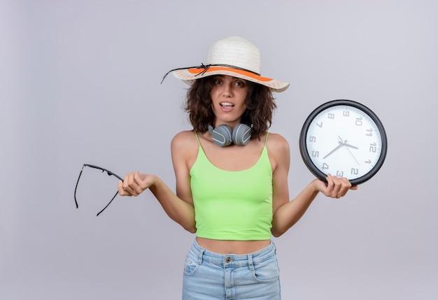 Zaskakująca młoda kobieta z krótkimi włosami w zielonej bluzce w słuchawkach ubrana w kapelusz przeciwsłoneczny, trzymając okulary przeciwsłoneczne i zegar ścienny na białym tle
