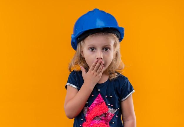 Zaskakująca piękna mała dziewczynka o blond włosach w granatowej koszuli i niebieskim hełmie trzymająca dłoń na ustach na pomarańczowej ścianie