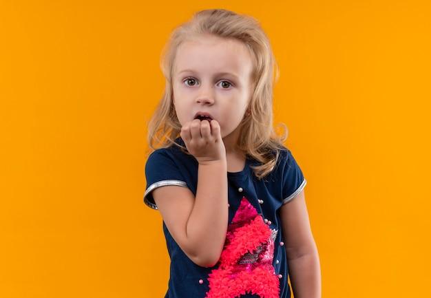 Zaskakująca piękna mała dziewczynka o blond włosach w granatowej koszuli trzymająca rękę na brodzie na pomarańczowej ścianie