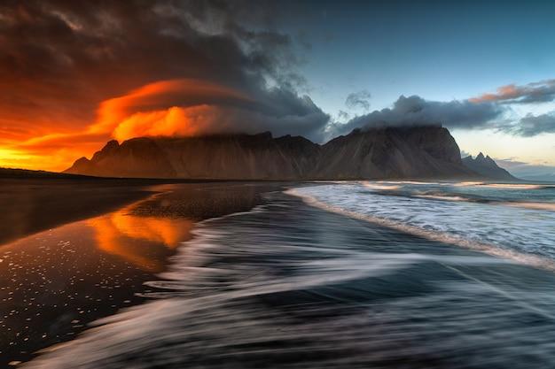 Zaskakująco piękna sceneria piaszczystej plaży i morza z zapierającymi dech w piersiach chmurami na niebie