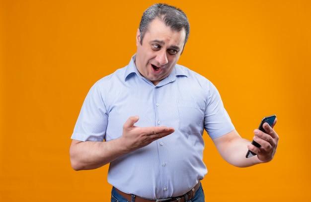Zaskakujący mężczyzna w niebieskiej koszuli w paski rozmawia przez połączenie wideo za pomocą telefonu komórkowego, stojąc na pomarańczowym tle