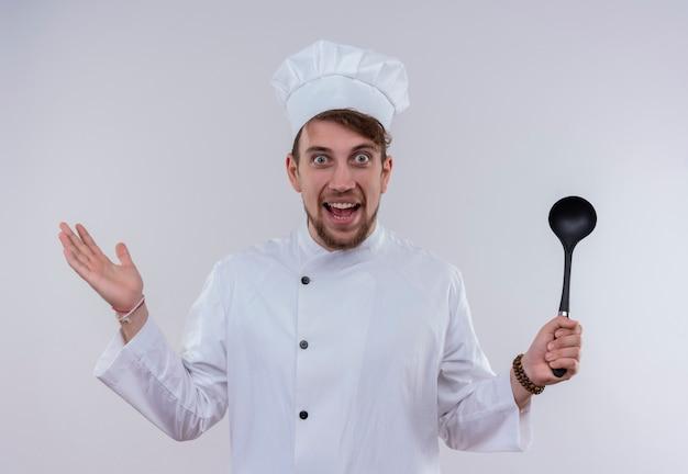 Zaskakujący młody brodaty szef kuchni w białym mundurze, trzymając czarną chochlę, patrząc na białą ścianę