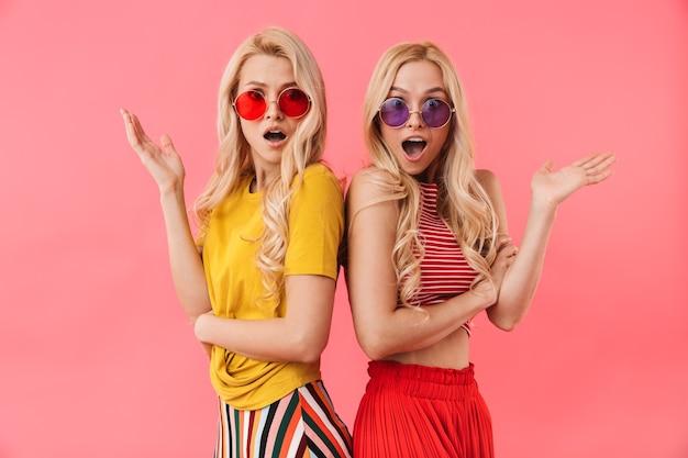 Zaskoczeni blond bliźniacy w okularach przeciwsłonecznych, gestykulujący i z otwartymi ustami nad różową ścianą