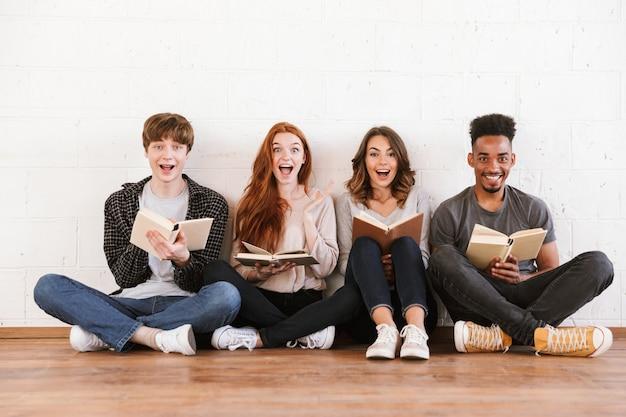 Zaskoczeni, emocjonalni młodzi przyjaciele studenci czytający książki.