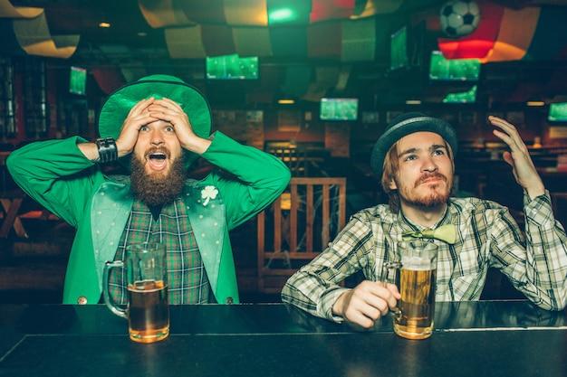 Zaskoczeni i zdenerwowani młodzi mężczyźni siedzą przy barze w pubie. patrzą do przodu i kibicują. chłopaki niezadowoleni. mężczyzna po lewej nosi kufle piwa.