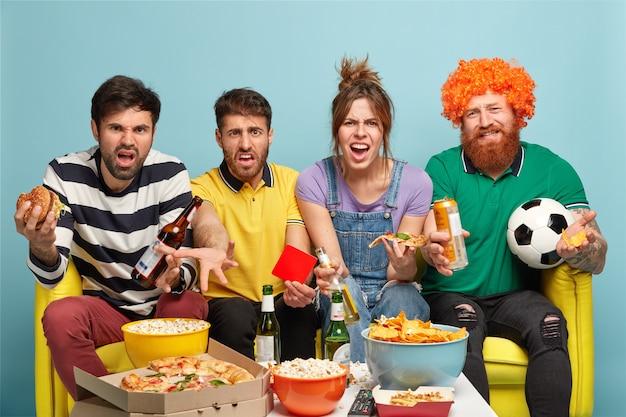 Zaskoczeni kibice czują się niezadowoleni, gdy ich ulubiona drużyna dostała czerwoną kartkę, jedzą fast food, siadają na wygodnej kanapie odizolowanej od błękitnej ściany. sport, ostrożność, gra, koncepcja telewizji.