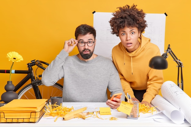Zaskoczeni profesjonalni inżynierowie płci żeńskiej i męskiej wspólnie opracowują plany, tworząc plany przyszłego projektu, oszołomione, aby dowiedzieć się, jak wielka pomyłka stanowi na pulpicie ze szkicami wokół. koncepcja pracy zespołowej