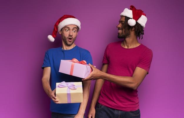 Zaskoczeni przyjaciele uszczęśliwieni nadejściem świąt bożego narodzenia z prezentem.
