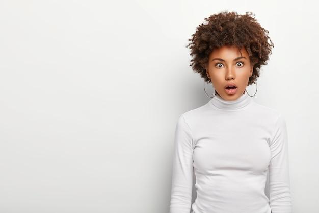 Zaskoczona afro amerykanka trzyma usta otwarte ze zdumienia, wystraszona zaskoczona miną, ubrana niedbale, odizolowana na białej ścianie z pustą przestrzenią po prawej stronie. koncepcja omg.