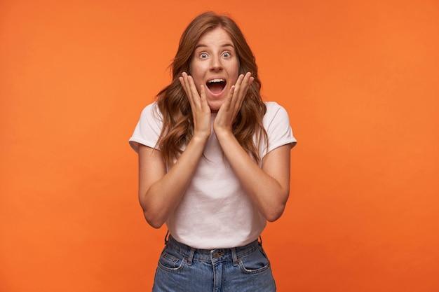 Zaskoczona atrakcyjna kobieta z kręconymi rudymi włosami trzymająca dłonie na twarzy, patrząca z szeroko otwartymi ustami i unosząca brwi, odizolowana