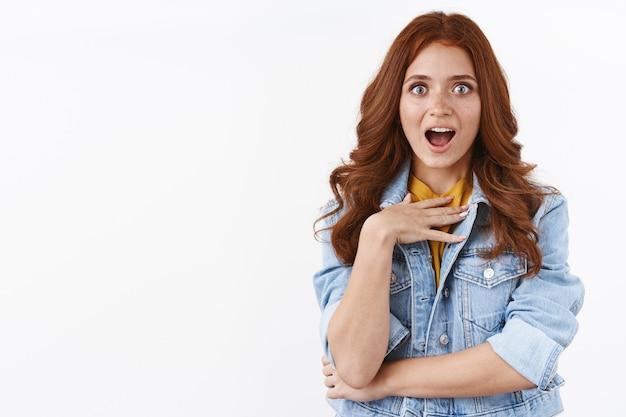 Zaskoczona atrakcyjna rudowłosa dziewczyna w dżinsowej kurtce, wygląda na zaskoczoną i pod wrażeniem, dotyka klatki piersiowej ze zdumienia, dysząc i gapiąc się na aparat, otrzymuje nieoczekiwaną nagrodę, biała ściana
