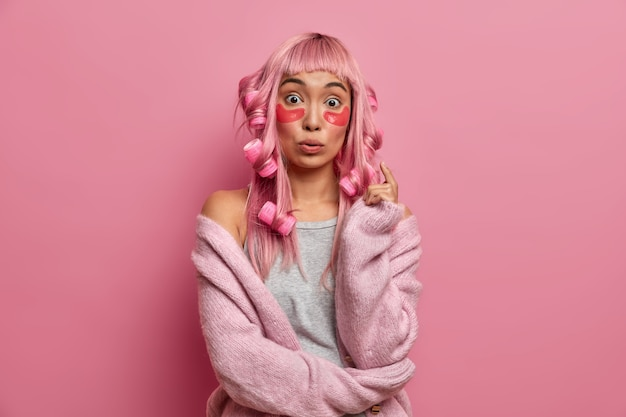 Zaskoczona azjatka o różowych włosach, podczas porannego szczytu nakłada lokówki, plastry kolagenowe, poddaje się zabiegom pielęgnacyjnym