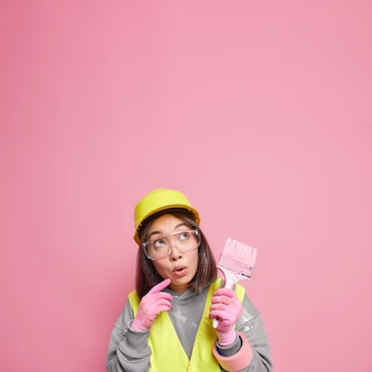 Zaskoczona azjatka skupiona, myśli o remontu mieszkania, trzyma pędzel do malowania