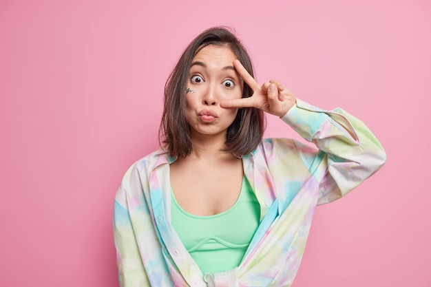 Zaskoczona azjatycka nastolatka o ciemnych włosach sprawia, że znak v nad okiem pokazuje gest disco, który trzyma usta złożone, nosi casualową wielokolorową koszulę na białym tle nad różową ścianą. koncepcja języka ciała