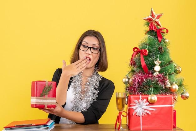 Zaskoczona biznesowa dama w garniturze w okularach pokazująca prezent i siedząca przy stole z choinką w biurze