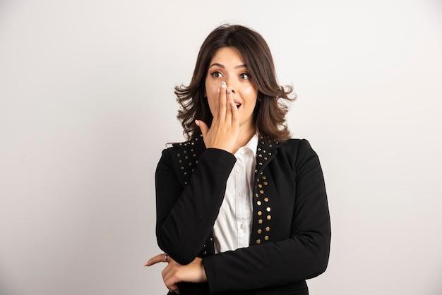 Zaskoczona bizneswoman zakrywa usta po usłyszeniu wiadomości