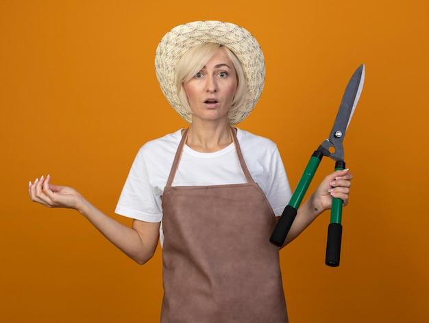 Zaskoczona blond ogrodniczka w średnim wieku w mundurze w kapeluszu, trzymająca nożyce do żywopłotu pokazująca pustą rękę odizolowaną na pomarańczowej ścianie