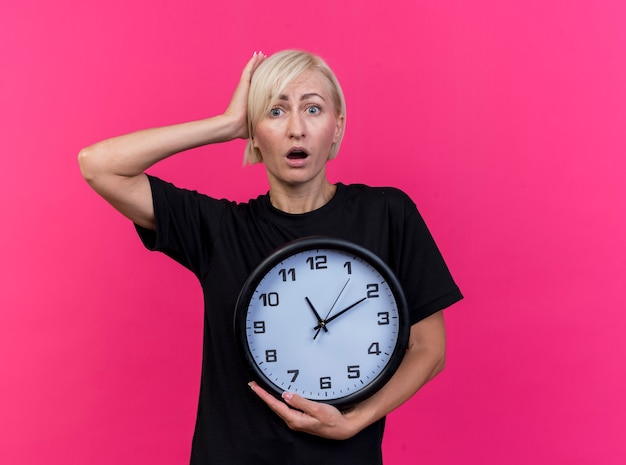 Zaskoczona blond słowiańska kobieta w średnim wieku, patrząc na kamerę, trzymając zegar, kładąc rękę na głowie na białym tle na szkarłatnym tle z miejsca na kopię