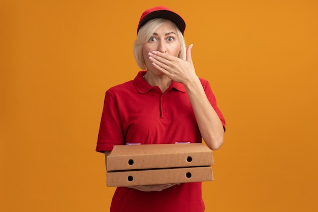 Zaskoczona blondynka dostarczająca w średnim wieku w czerwonym mundurze i czapce, trzymająca paczki z pizzą i trzymająca rękę na ustach