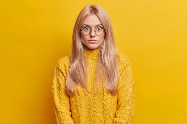 Zaskoczona blondynka stoi bez słowa w pomieszczeniu, nosi okrągłe przezroczyste okulary ubrane w żółty sweter pozuje w pomieszczeniu. zaskoczona i pod wrażeniem europejka wpatruje się w wytrzeszczone oczy.