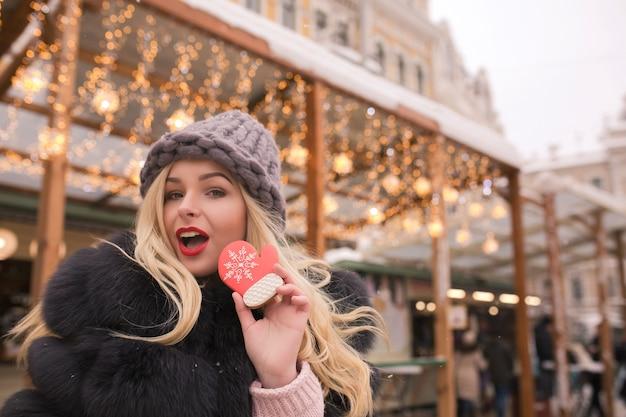 Zaskoczona blondynka trzymająca aromatyczne świąteczne pierniczki na tle lekkiej dekoracji na jarmarku bożonarodzeniowym w kijowie
