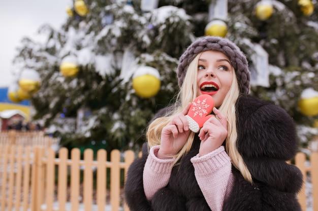 Zaskoczona blondynka ubrana w futro i czapkę z dzianiny, je smaczny świąteczny piernik na tle lekkiej dekoracji na ulicy
