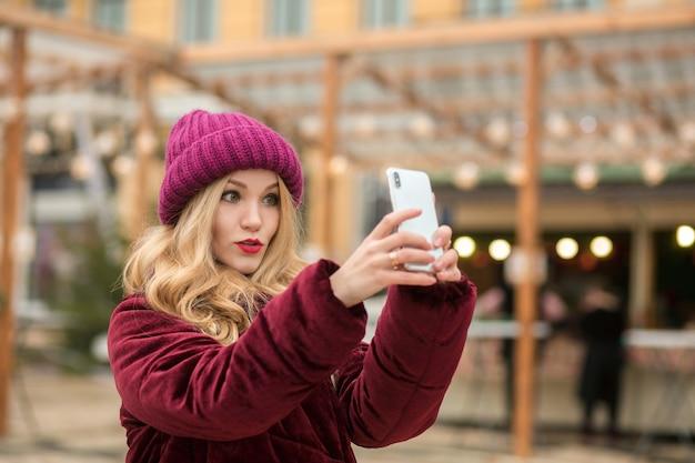 Zaskoczona blondynka ubrana w modne ciuchy robi selfie na tle świateł w kijowie