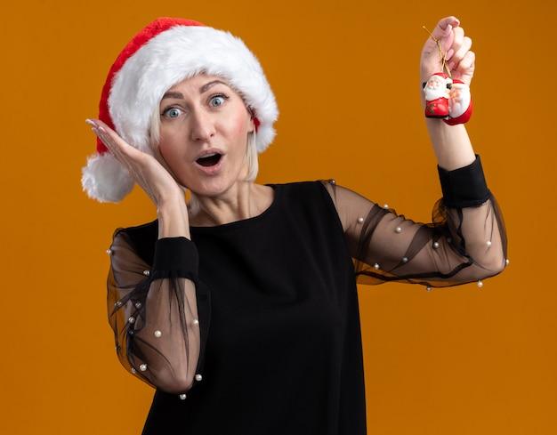 Zaskoczona blondynka w średnim wieku w świątecznym kapeluszu patrząca na podnoszenie świętego mikołaja ozdób choinkowych trzymająca rękę przy głowie odizolowaną na pomarańczowej ścianie