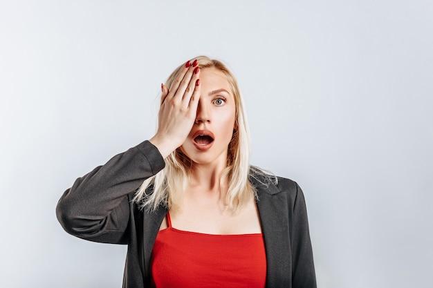 Zaskoczona blondynka zakrywa dłonią połowę twarzy. kobieta zapamiętała, nauczyła się i zrozumiała ważne informacje dotyczące firmy. pojedyncze tło dla reklamy.